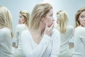 frightened young woman seeing multiple reflections of herself in mirrors
