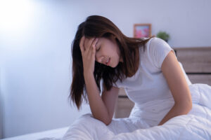 woman with a migraine headache in the morning in bed