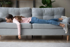 Full length of girl lying rest at home in living room buried her face in couch feels exhaustion