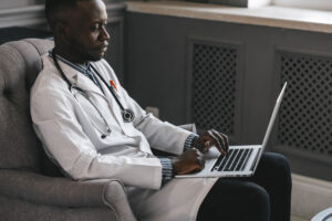 male black doctor online with a laptop computer with a serious look on his face